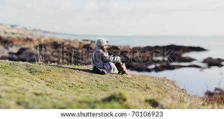 Girl sitting on the grass of a cliff, watching the horizon - stock photo