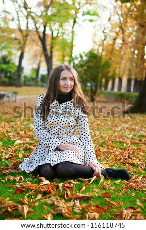 Girl sitting on the ground in park on a fall day - stock photo