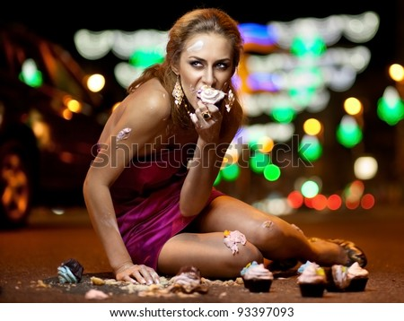 Girl sitting on the road and eating cake - stock photo