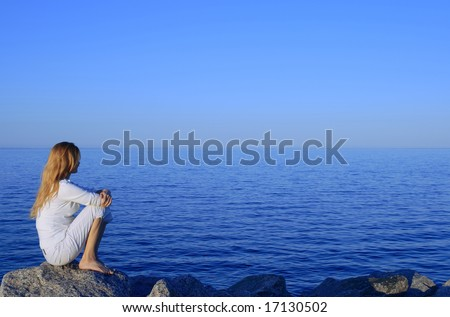 Girl sitting on the rock by the peaceful sea at sunset. - stock photo