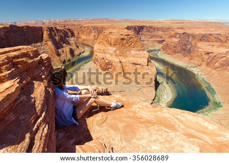 girl sitting on the rocks in front of Horseshoe Bend - stock photo