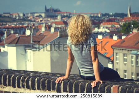girl sitting on the roof of a house in Prague. top view of the city. top view . lifestyle - stock photo