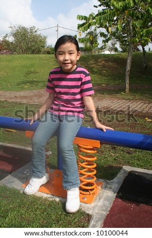 Girl sitting on the seesaw at the playground in the park - stock photo