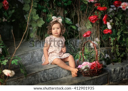 girl sitting on the stone steps in a pink dress with a basket of roses with curls - stock photo