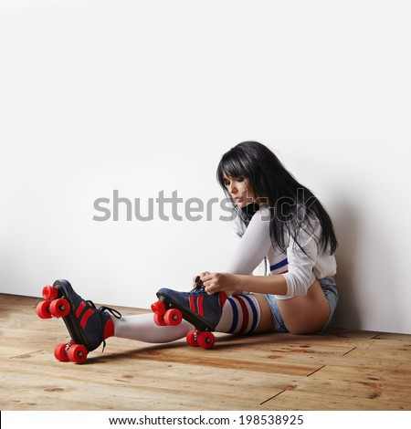 girl, sitting on the wooden floor, and put on her vintage roller skates - stock photo