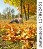 Girl sitting on the yellow autumn leaves carpet - stock photo
