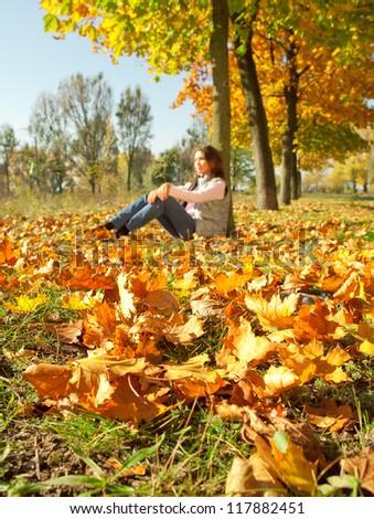 Girl sitting on the yellow autumn leaves carpet - stock photo