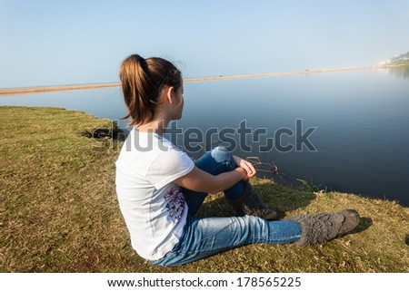 Girl Sitting River Water Lagoon Teen girl relaxing sitting by beach sea river lagoon waters on a calm blue day in the countryside - stock photo