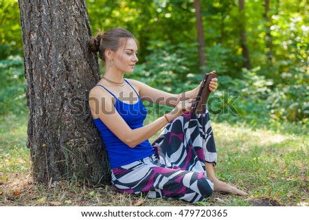 girl sitting under a tree on the ground with the gadget in hand