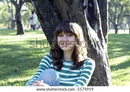girl sitting under tree - stock photo