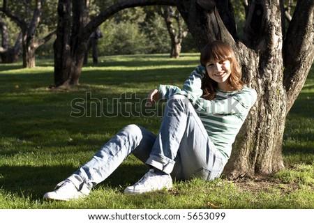 Girl sitting under tree at autumn - stock photo