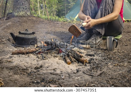 Girl sitting while camping near the bonfire close to tent and fry bread