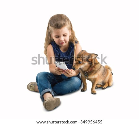 girl sitting with a phone and shows the dog - stock photo