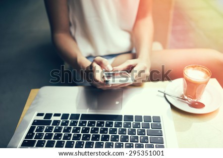 girl sitting with a phone in her hands, the laptop on the desk. Young student. focus on phone and laptop keyboard, flare light, cross process.  - stock photo