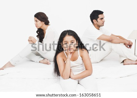 Girl sitting with her parents on the bed looking serious - stock photo