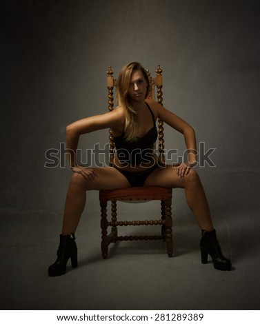 girl sitting with open legs, under yellow light - stock photo