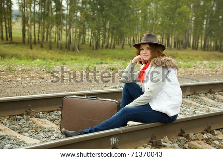 girl sitting with suitcase along the train tracks - stock photo