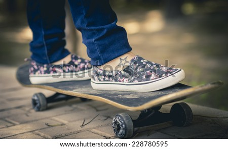 Girl skateboarding on a park - stock photo