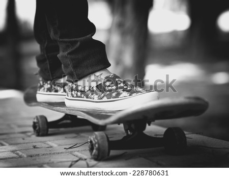 Girl skateboarding on a park in black and white  - stock photo
