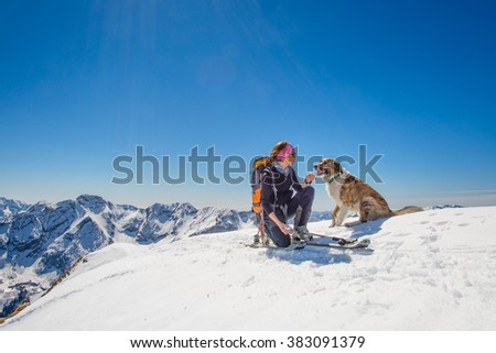 Girl ski touring with his dog at the top of the mountain - stock photo
