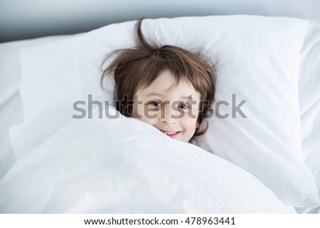 Girl sleeping in pajamas on white bed