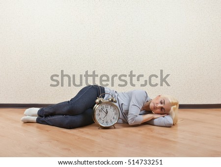Girl sleeping on the floor the empty room next to the clock