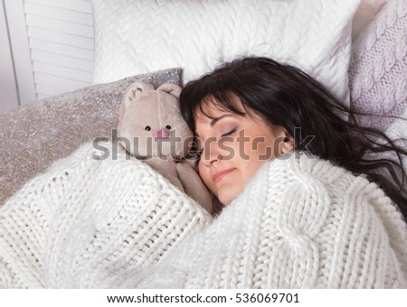 Girl sleeps in a bed with a toy a teddy bear