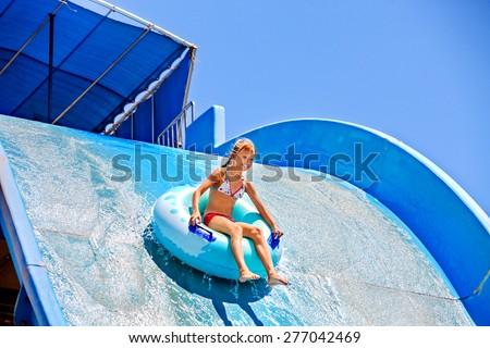 Girl slides down a very steep water slide at aquapark.  - stock photo
