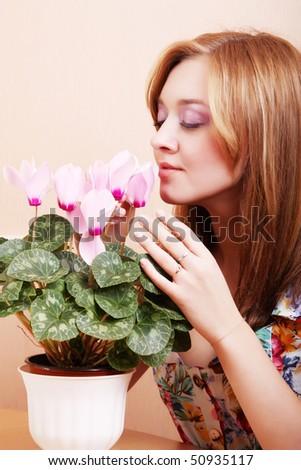 Girl smells flowers cyclamen - stock photo