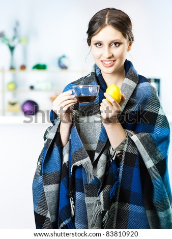 girl smile and drink tea with blanket in kitchen - stock photo