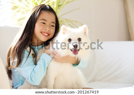 Girl smile snuggling the Spitz