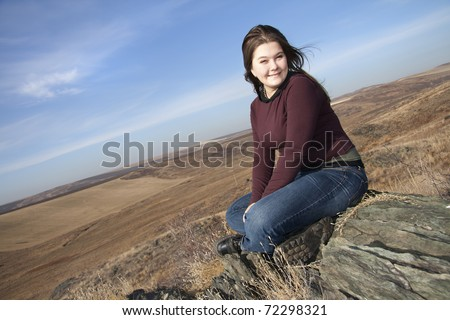 Girl smiles, sits on stones in the autumn. - stock photo