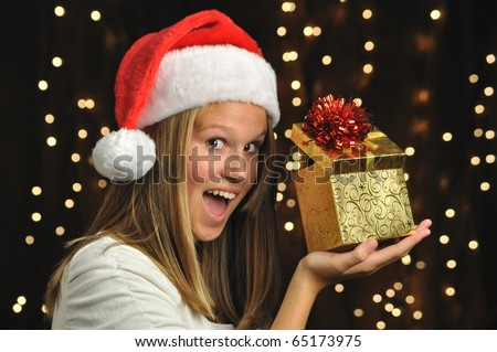 Girl Smiles with Open Gift. Teen girl with Santa hat on holds a gold wrapped present.