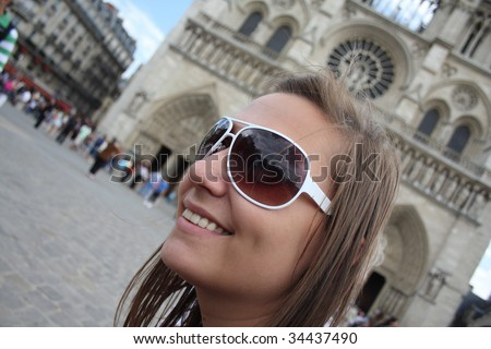 Girl smiling and enjoying her city trip in front of the Notre Dame - stock photo