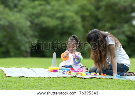 Girl smiling happily on the grass between the play toys  with her mother,mother day