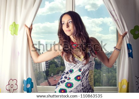 Girl smiling in front of window with blue cloudy sky - stock photo