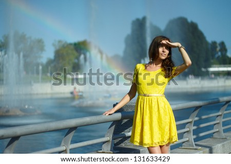 girl smiling in the sun in a yellow dress - stock photo