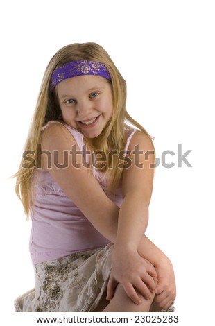 Girl smiling with crossed legs against a white background - stock photo