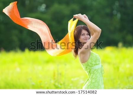girl smiling with scarf in field - stock photo
