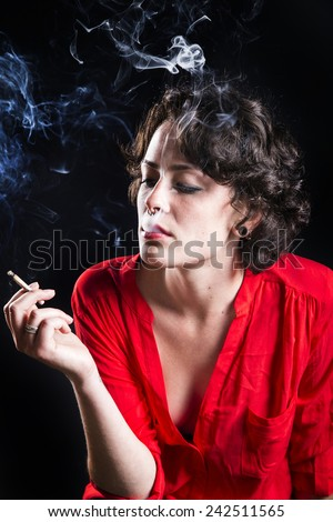girl smoking cigarette on black background - stock photo