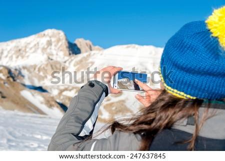 Girl snaps a photo of the mountain, Italy - stock photo