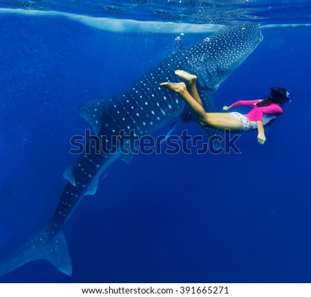 Girl snorkeling with whale shark