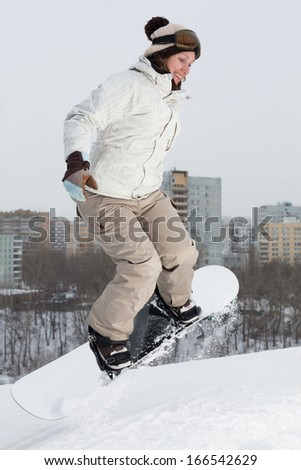 Girl snowboarder jumping on the snow on a hill  - stock photo
