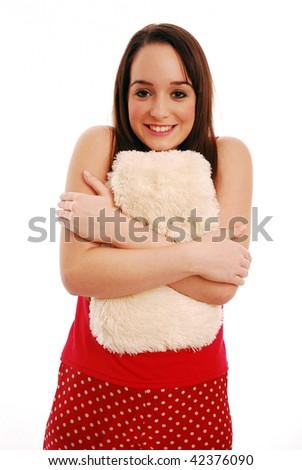 Girl snuggling up to hot water bottle on white background - stock photo