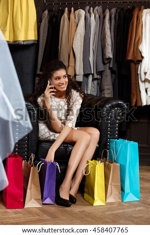 Girl speaking on phone, sitting in shopping mall with buyings.