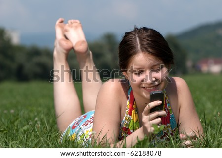 Girl speaks by mobile phone against summer green nature - stock photo