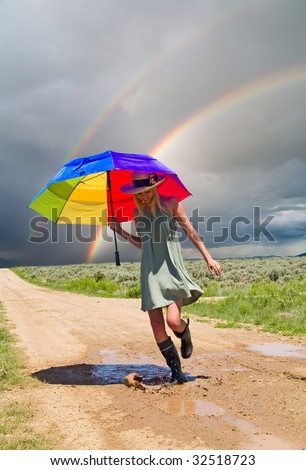 Girl splashing water in a puddle after a rain - stock photo
