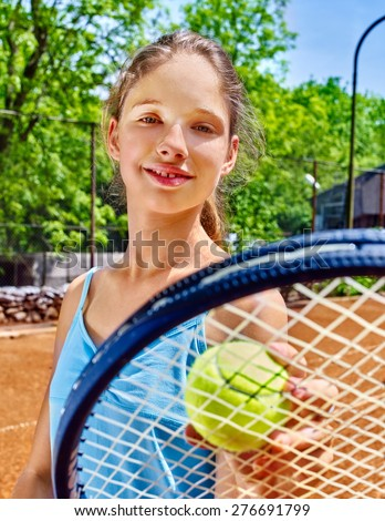 Girl sportsman with racket and ball on  tennis court. Green tree ang blue sky on background. - stock photo
