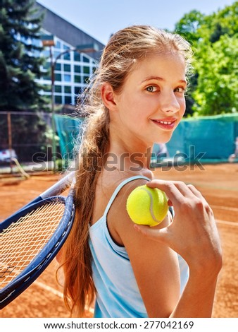 Girl sportsman with racket and ball on  tennis court. Green tree ang blue sky on background. Looks over her shoulder. Stadion on background. - stock photo