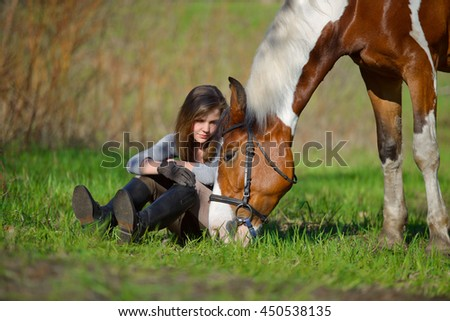 Girl sportswoman and her horse after a riding in the spring